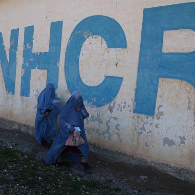 Kaksi burkhaan pukeutunutta naista ohittaa suuren UNHCR-tekstin.