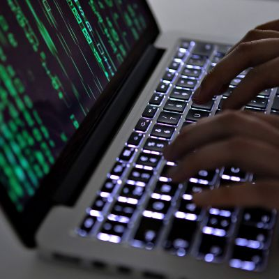 Henkilö hakkeroi kannettavaa tietokonetta. Lavastettu kuva.