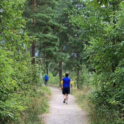 Mies lenkkeilee metsässä.