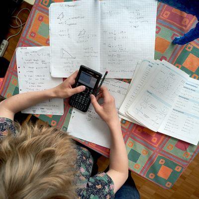 Koululainen tekee matematiikan tehtäviä.