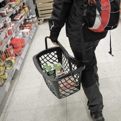 Nainen ostoskorin kanssa kaupassa.