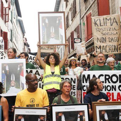 Mielenosoittajat pitävät Emmanuel Macronin potrettikuvia ilmassa G7-kokousta vastaan Bayonnessa, Ranskassa 25. elokuuta.
