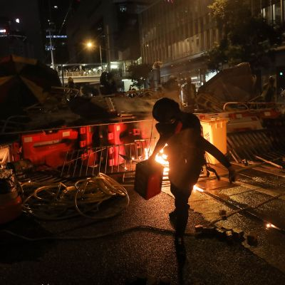 Mielenosoittaja kasaa barrikadia kadulla Hongkongissa.