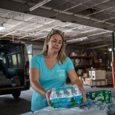 Rachel Costigan nostaa vesipulloja autosta pöydälle.