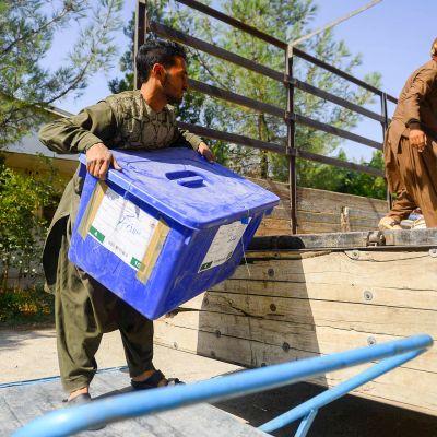 Vaalityöntekijät lastaavat äänestyslaatikoita kuorma-autoon.