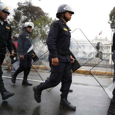 Mellakkavarusteisia poliiseja Perun parlamenttitalon edustalla Limassa.