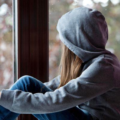 lapsi harmaassa hupparissa katsoo ulos ikkunasta