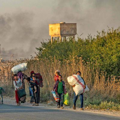 Siviilit pakenevat Turkin pommituksia Syyrian koillisosassa 9. lokakuuta.