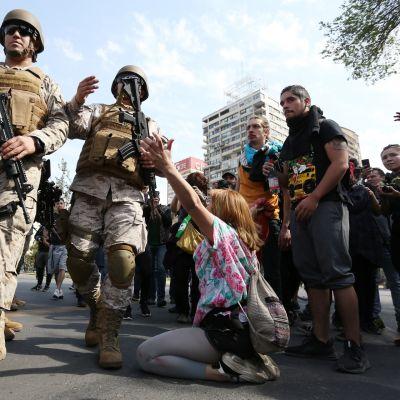Sotilaat yrittävät estää mielenosoittajia etenemästä Chilen pääkaupungissa Santiagossa 19 lokakuuta.