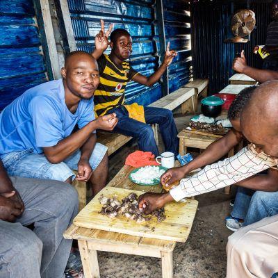 Miehet syövät lounasta  Etelä-Afrikassa.