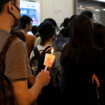 Tuhannet kynttiläkulkueeseen osallistuneet surivat perjantaina kuollutta opiskelijaa Hongkongissa.