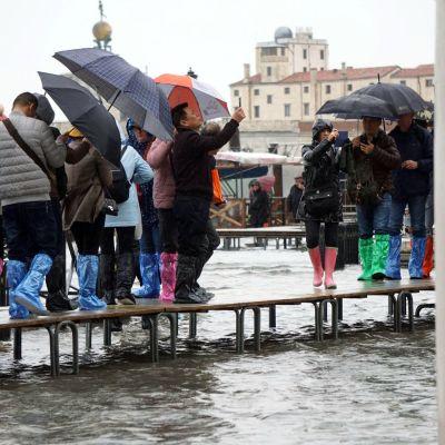 Ihmiset kävelivät penkeillä ja ottivat kuvia tulvivassa Venetsiassa tiistaina.