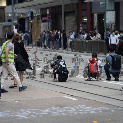 Hallintoa vastustavat mielenosoittajat ovat lamauttaneet liikennettä rakentamalla tiesulkuja Hongkongissa.