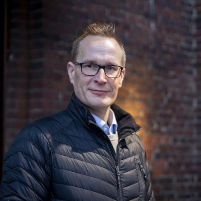 En man med glasögon och svart jacka står framför en tegelvägg.