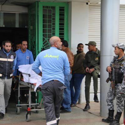 Ensihoitajat kuljettavat turistibussin kolarissa loukkaantunutta uhria Suezin sairaalaan.