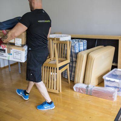 mies kantaa muuttolaatikoita