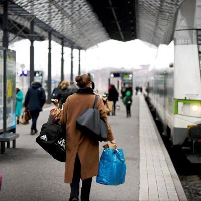 Matkustajia tavaroineen menossa Ouluun lähtevään junaan Helsingin Rautatieasemalla