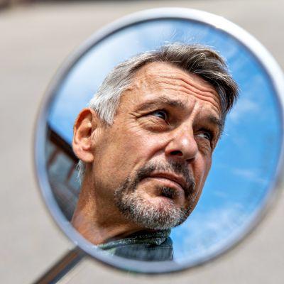 Miehen kuva näkyy moottoripyörän peilistä.