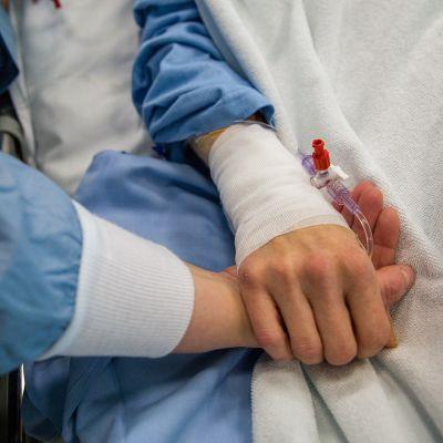Henkilö tukee hoidossa olevaa potilasta pitämällä sitä kädestä kiinni.
