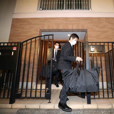 Miehet kantavat kasseja ulos asunnosta