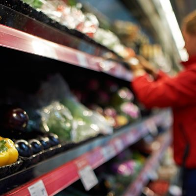 Työntekijä täyttää vihanneshyllyä supermarketissa.