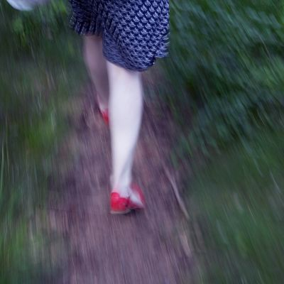 nainen juoksee polulla punaisissa kengissään