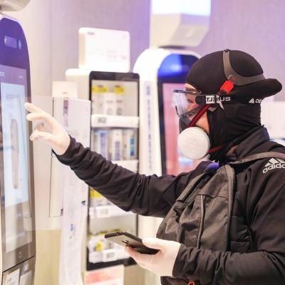 Täysin suojattu mies kaupan itsepalveluautomaatilla Wuhanissa.