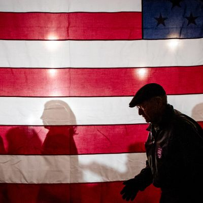 Ihmisiä kävelee USA lipun takana vaalitilaisuudessa.