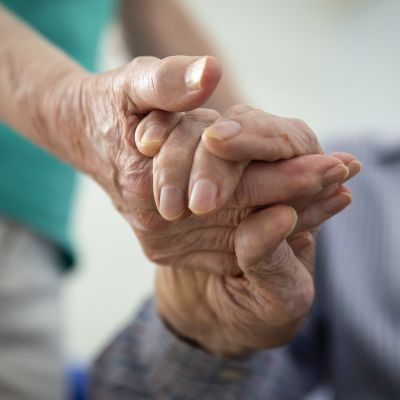 Vanhus pitää toista kädestä.