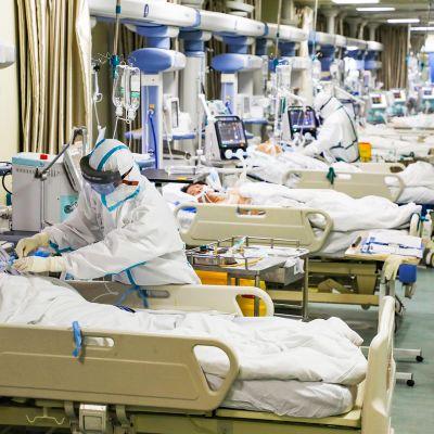 Hoitohenkilökunta hoitaa sairastuneita Wuhanin sairaalassa.