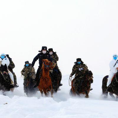 Rajaviranomaiset matkaavat lumen läpi tutkiakseen vuoristoista raja-aluetta ja toimittaakseen tietoja koronaviruksesta. Kiinan Xtajiangin maakunnan Altayn syrjäisen alueen asukkaille.