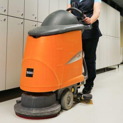 Siivoja tyntää lattian pesukonetta käytävällä.