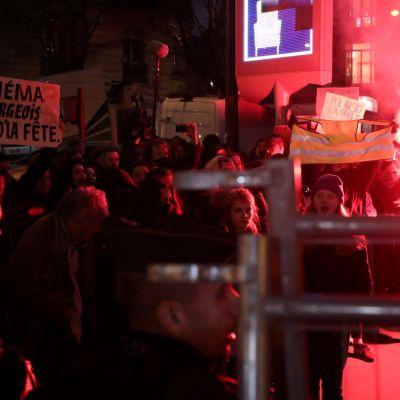 Mielenosoittajia kylttien ja soihtujen kanssa Salle Pleyel -salin edessä.