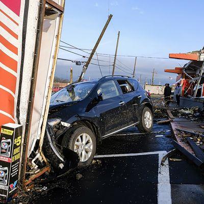 Tornadon tuhoamia rakennelmia ja auto.