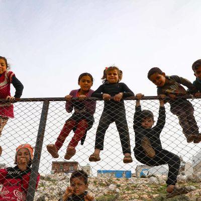 Lapset kiipeilevät aidalla