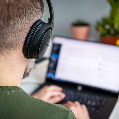 Mies työskentelee etänä kannettavalla tietokoneella.