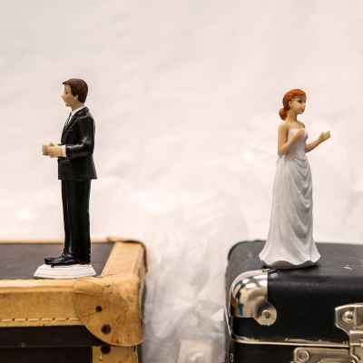 Ett bröllopspar (två figurer, kakdekorationer) står på kappsäckar och tittar bort från varandra.