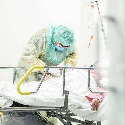Hoitaja ottaa näytettä koronaepäillyltä koronapotilaiden testaamiseen ja hoitoon tarkoitetulla osastolla Turun yliopistollisessa keskussairaalassa