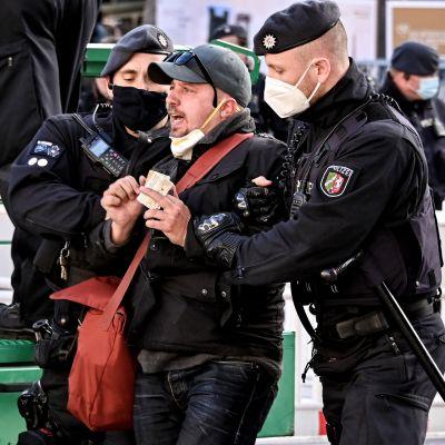 Poliisi ottaa kiinni miehen, joka otti osaa korona-aiheiseen mielenosoitukseen Kölnissä