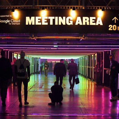 Slushin vierailijoita hämärässä käytävässä jossa värivaloja