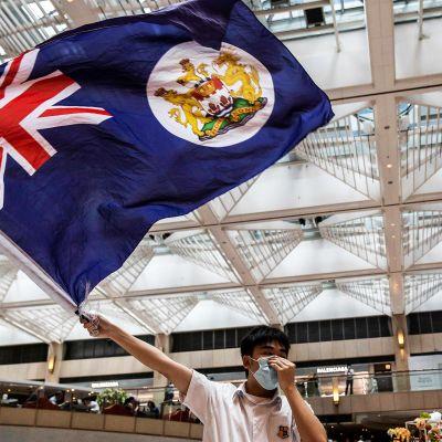 Mielenosoittaja heiluttaa Hongkongin siirtomaa-ajan lippua.