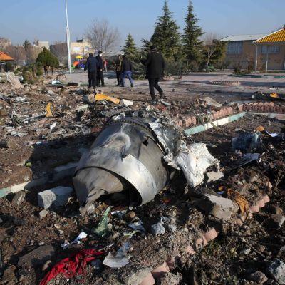 Pelastustyöntekijät Teheranissa maahan syöksyneen lentokoneen jäänteiden keskellä.