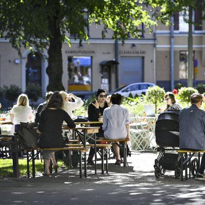 Ihmisiä Karhupuiston lippakioskin terassilla Helsingissä 12. kesäkuuta 2020.