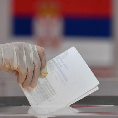 Suojakäsineellä peitetty käsi jättämässä äänestyslipuketta äänestyspaikalla Belgradissa, Serbiassa.