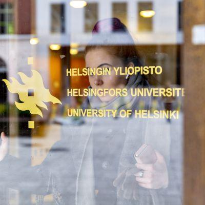 Nainen on kävelemässä Helsingin Yliopiston ulko-ovesta ulos.