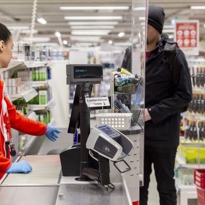 Kassatyöntekijä palvelee asiakasta suojakäsineitä käyttäen Helsingin Citycenterin Tokmannilla