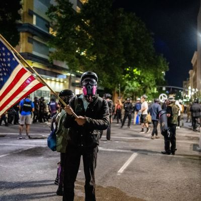 Mielenosoittaja pitää Yhdysvaltain lippua mielenosoitusten keskellä Portlandissa.