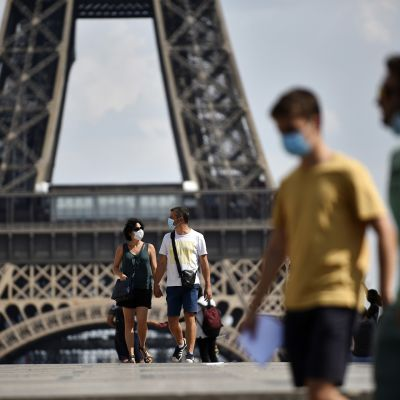 Ihmisiä suojamaskeissaan Eiffel-tornin juurella