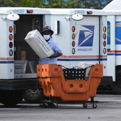 Yhdysvaltain postilaitoksen työntekijä tekee töitä kasvimaski kasvoillaan.