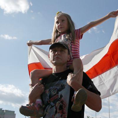 Lapsi piteli Valko-Venäjän vanhaa lippua lauantain mielenosoituksessa.